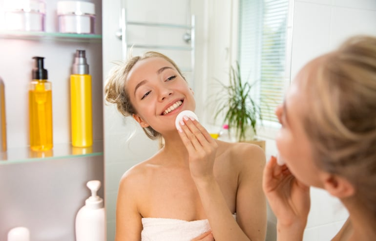 Woman applying niacinamide toner for hydrated, glowing skin