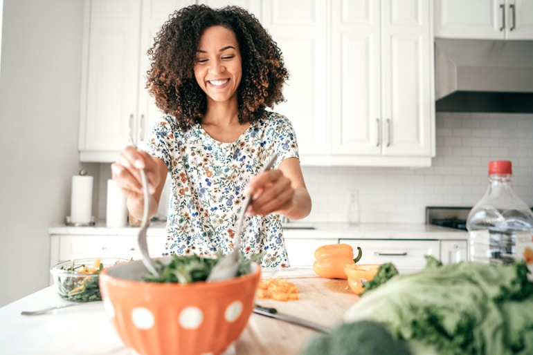 Woman mixing a salad with lettuce and dark leafy greens