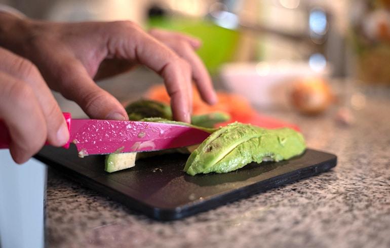 Mujer cortando aguacate para obtener grasas saludables en su almuerzo