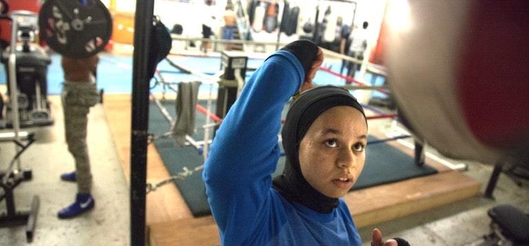 La boxeadora Amaiya Zafar golpea una bolsa en el gimnasio de boxeo, alimentada por alimentos saludables de su diario de alimentos.