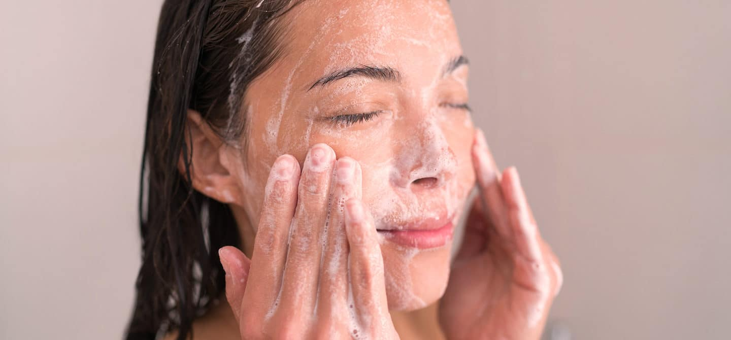 Woman washing her face and following sustainable skincare tips for environmental concerns