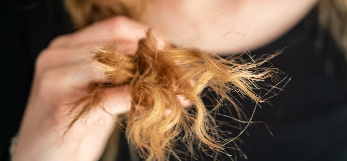 Red-headed woman showing her hair breakage and split ends that need repair