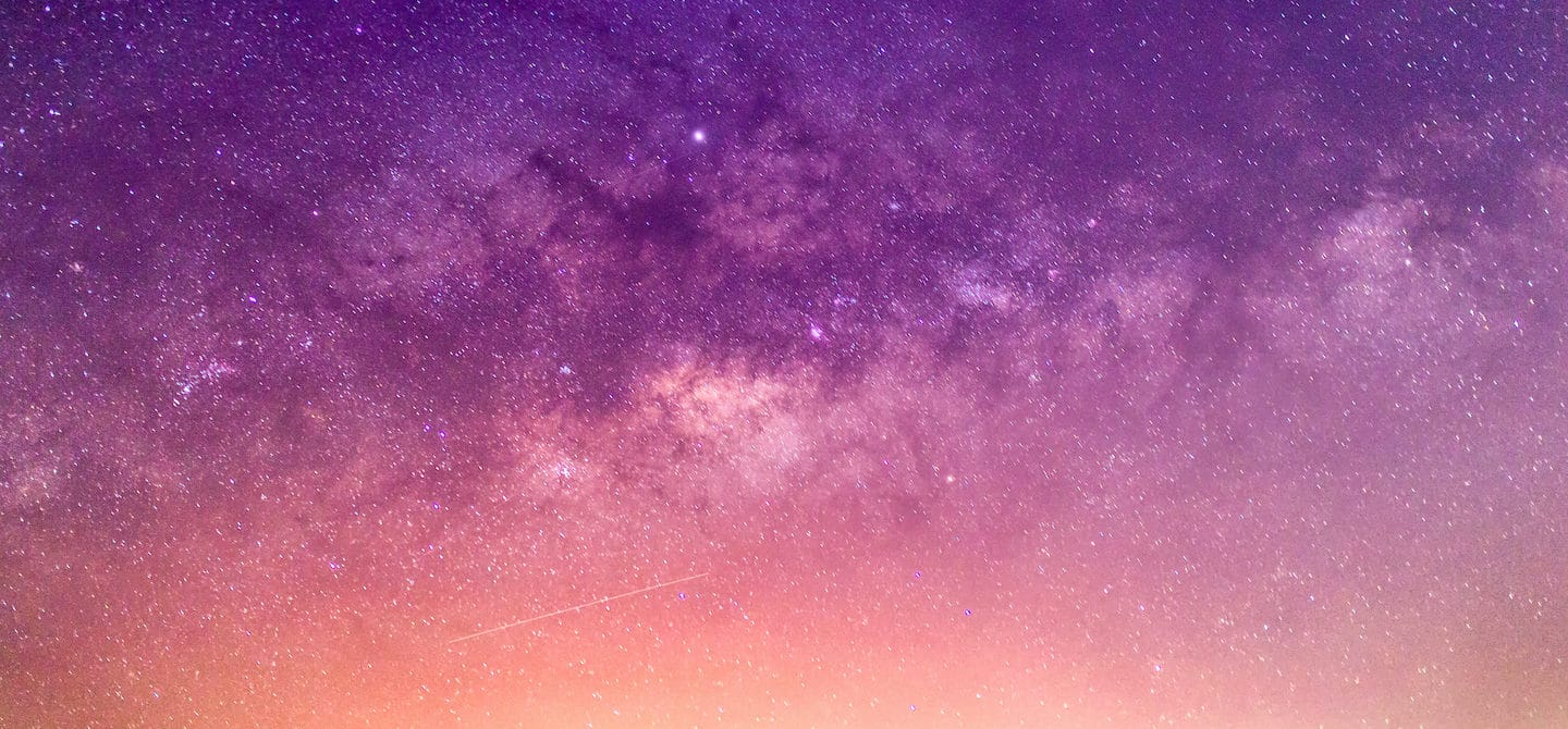 Purple, orange, and pink starry sky for astrology concept and April 2021 wellness horoscopes