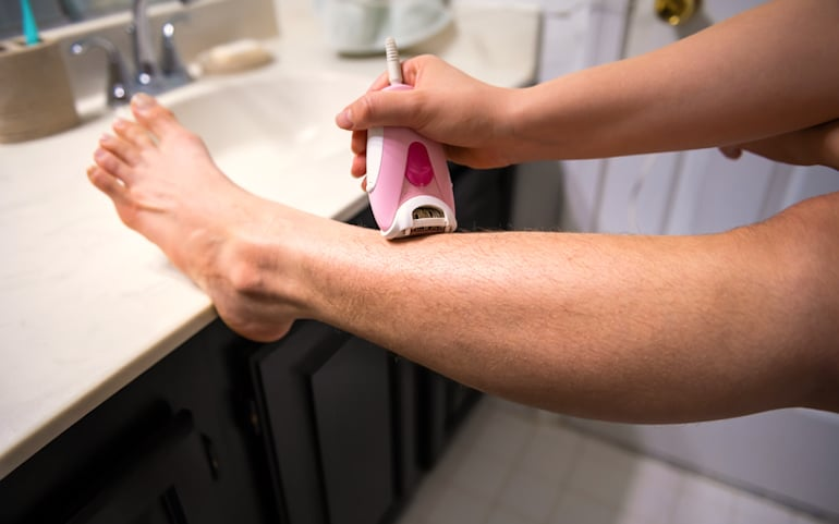 Woman with hirsutism (excess hair growth) shaving her legs with an electric razor