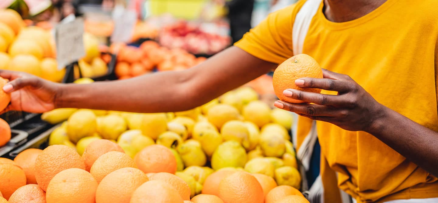 Woman buying citrus fruits at the farmers market as one method to eat more sustainably