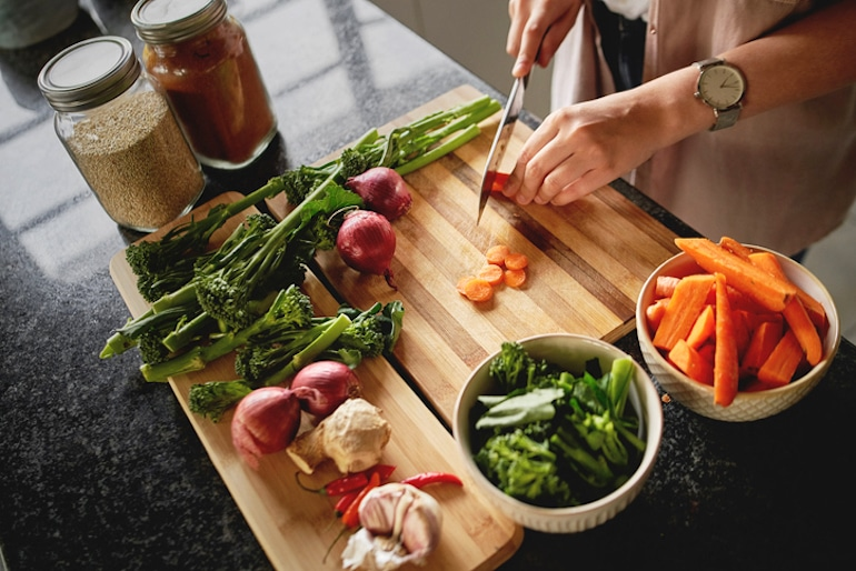 Angled shot from above on a woman chopping vegetables on a cutting board;  concept of a healthy diet