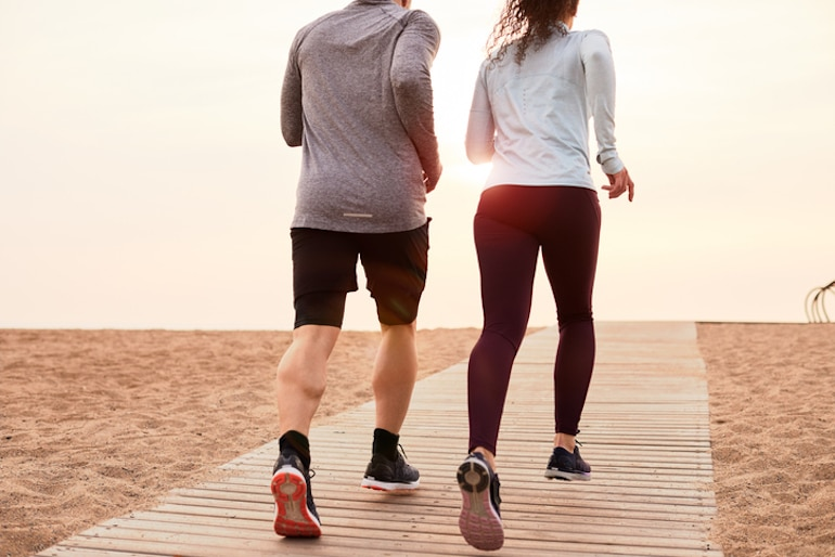 Couple exercising on the beach to help yield weight loss results