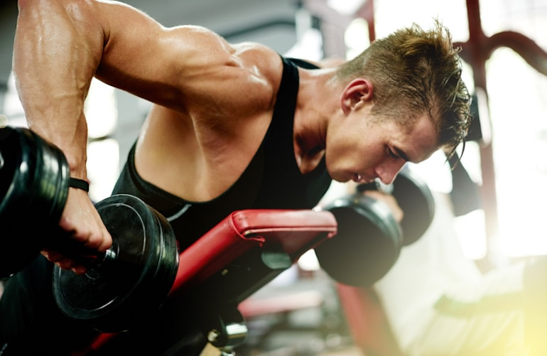 Man sweating while lifting weights at the gym