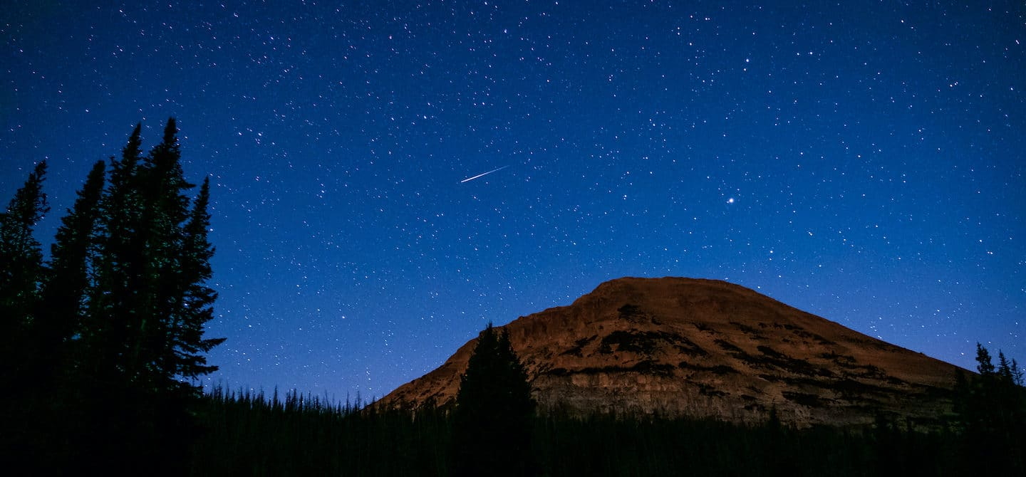 Starry night sky in a mountain desert landscape; astrology and wellness horoscopes concept