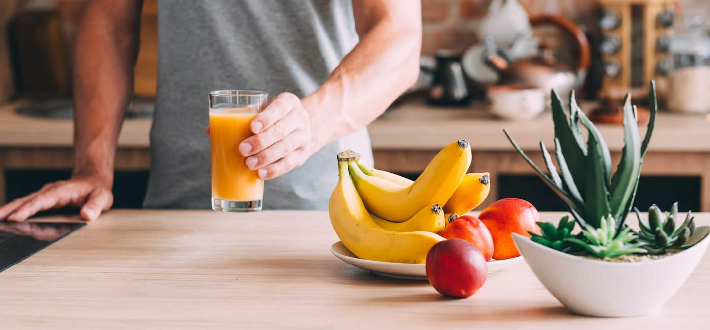 Man in kitchen holding juice with bananas and apples to help reduce bloating