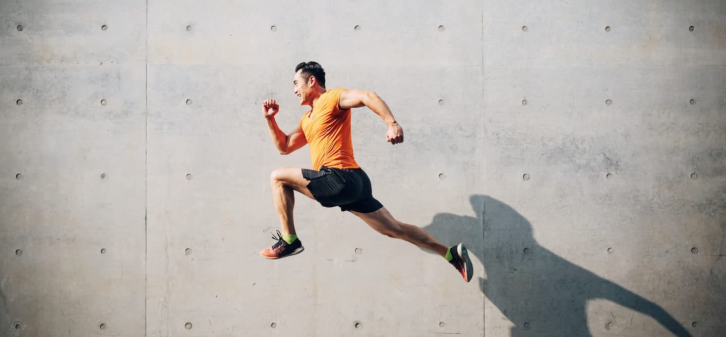 Sporty man jumping in the air to illustrate the best vitamins for energy