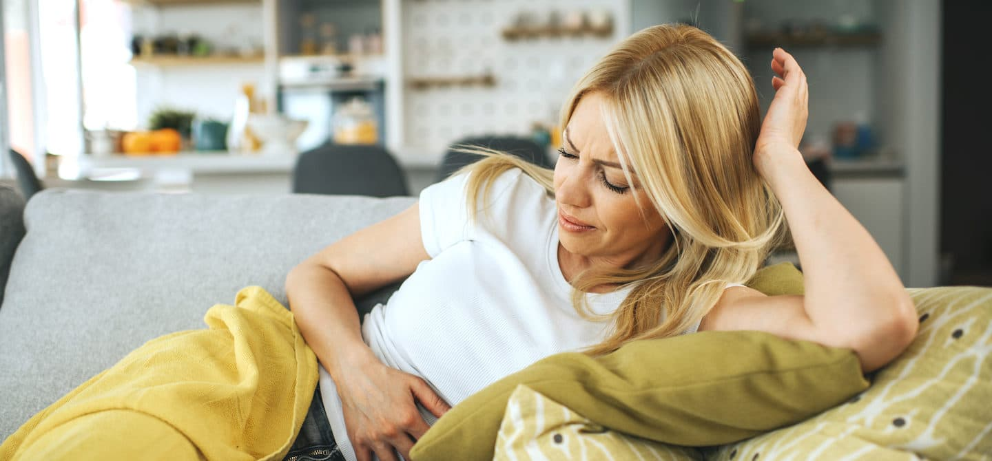 Woman wincing from period pain on the couch, trying to understand its causes and tips for relief