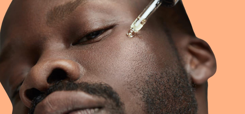 Man applying vitamin C serum to benefit his skin
