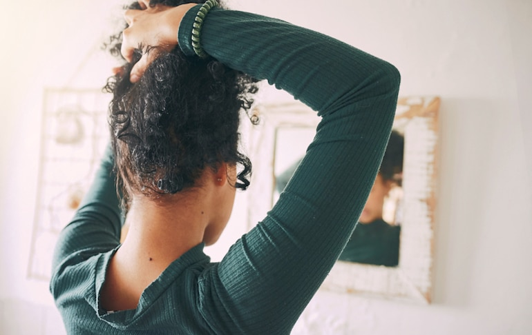 Woman looking in the mirror tying her hair up tightly, which can contribute to hair breakage