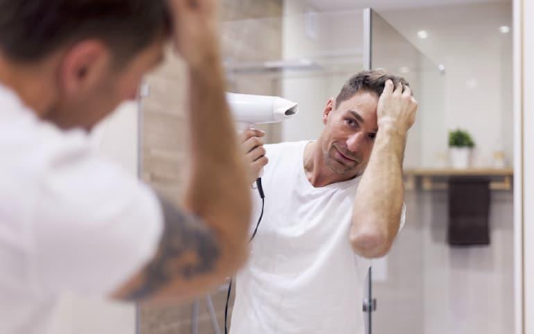 El hombre seca groseramente el cabello a alta temperatura, lo que puede dañar el cabello.