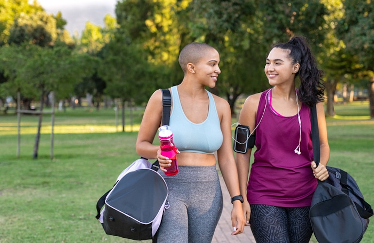 Two female friends walking in the park to get light exercise to help stop period pain naturally