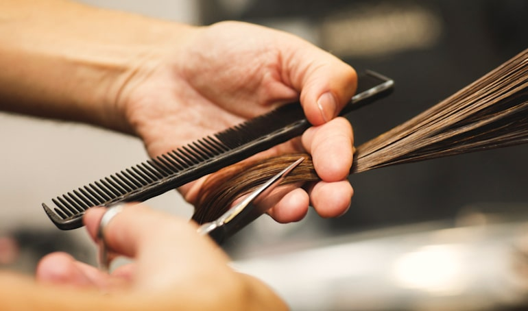 Hair stylist trimming a brunette's hair to help stop hair breakage and repair split ends