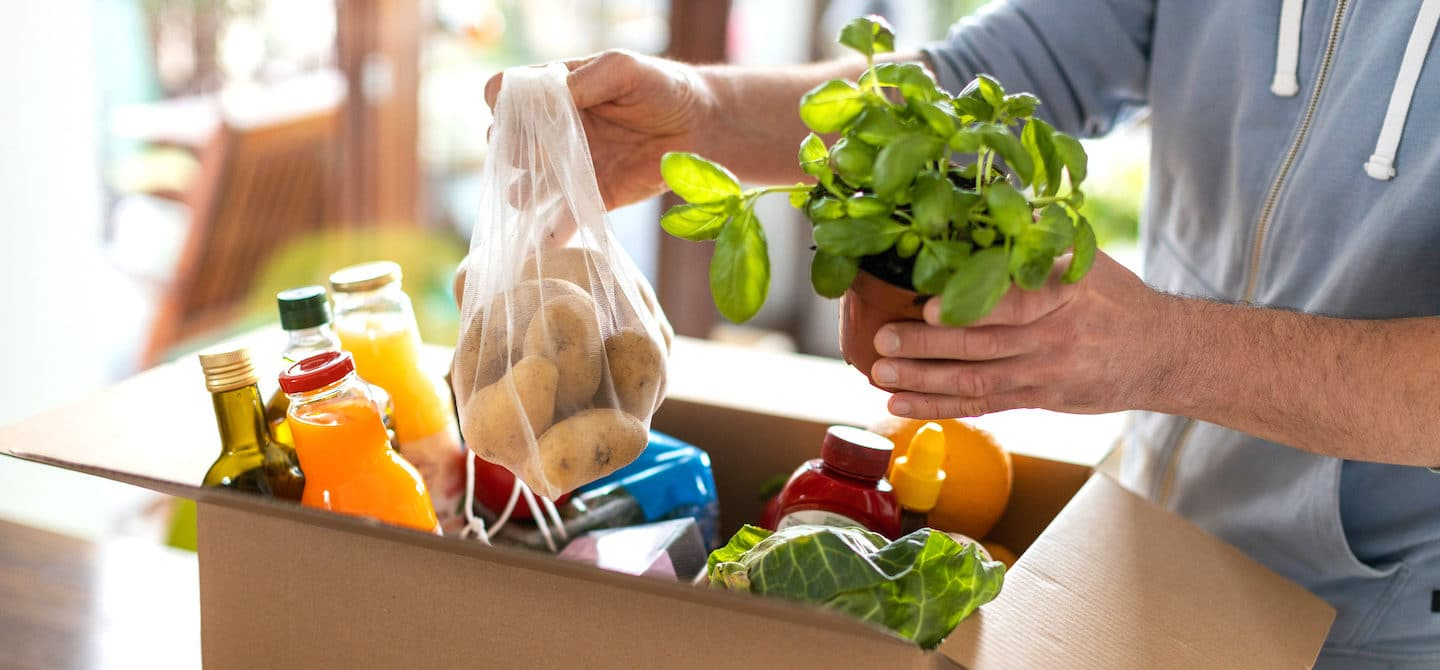 Man unpacking his grocery haul with plant-based foods, rich in benefits for human and environmental health