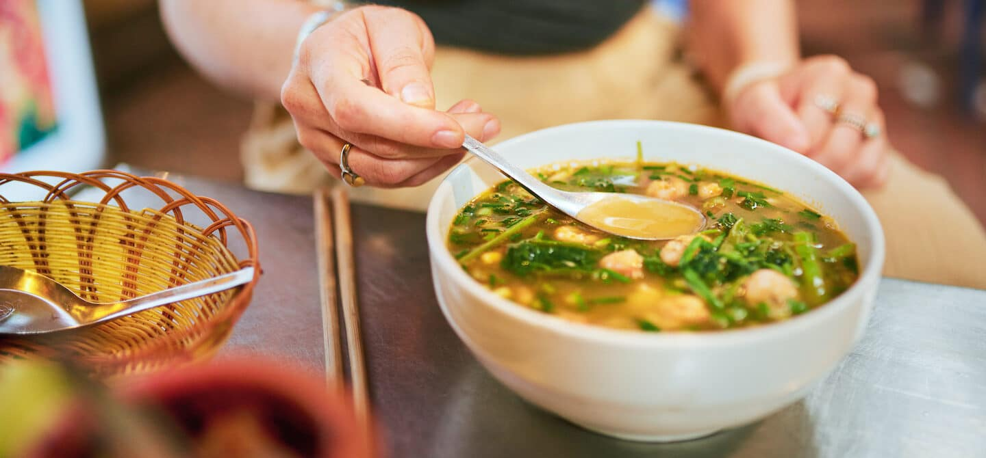 Young woman eating bone broth, a food high in collagen, at a restaurant for anti-aging benefits