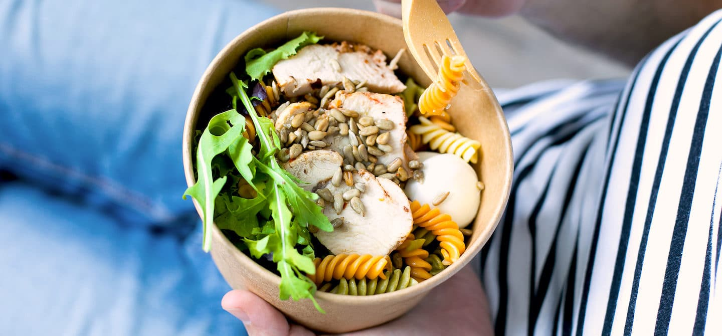 Eating a bowl with chicken and sunflower seeds, two of the best foods to eat for hair growth