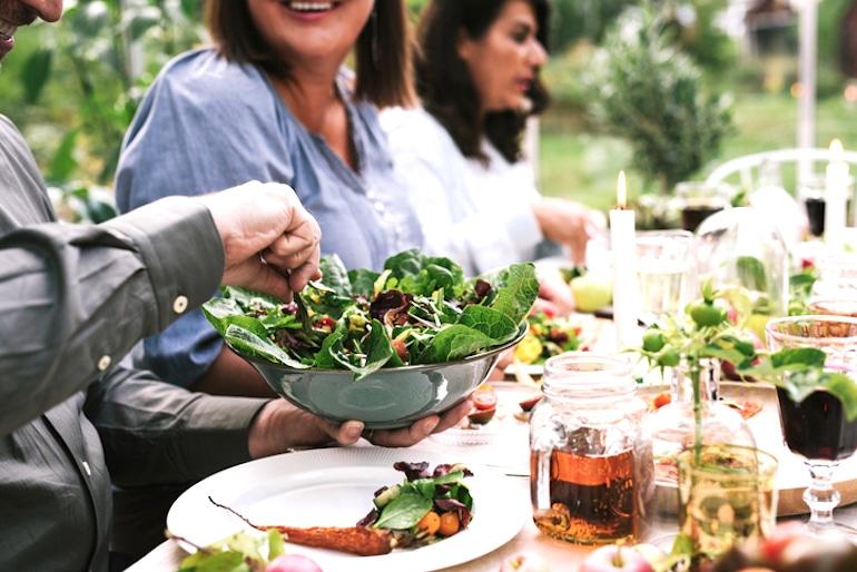 Amigos cenando al aire libre con una dieta a base de hierbas