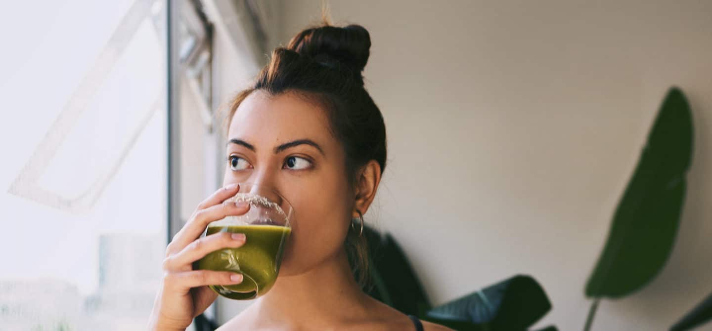Pensive woman drinking green juice by the window, wondering if you can really boost your immune system through diet and lifestyle