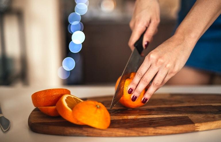 Mujer cortando naranja para lograr su ingesta de vitamina C para la inmunidad
