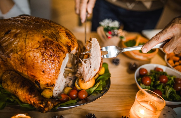 Man carving turkey on dinner table, which has tryptophan to promote mental and emotional well-being