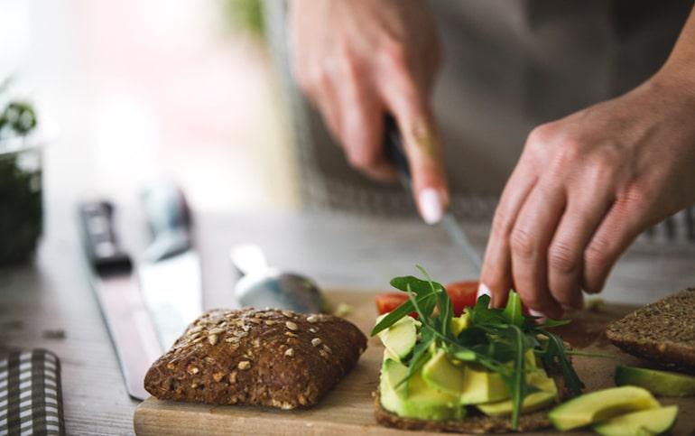 Persona que hace un sándwich vegetariano saludable con aguacate, tomate y arugala para mantenerse saludable a través de la dieta.