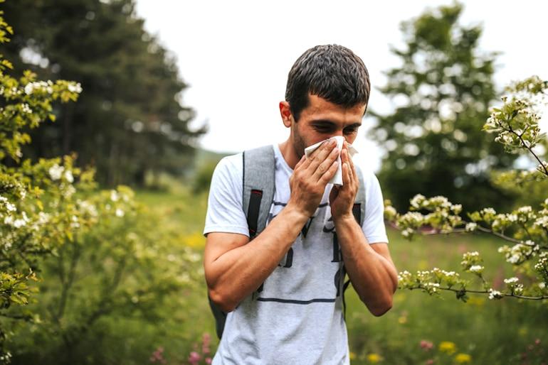 Hombre sonándose la nariz al aire libre para protegerse del polen y otros antígenos, ilustrando cómo funciona el sistema inmunológico