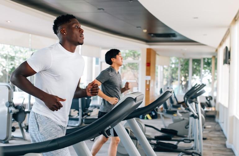 Dos hombres corriendo en cintas de correr en el gimnasio para apoyar el sistema inmunológico