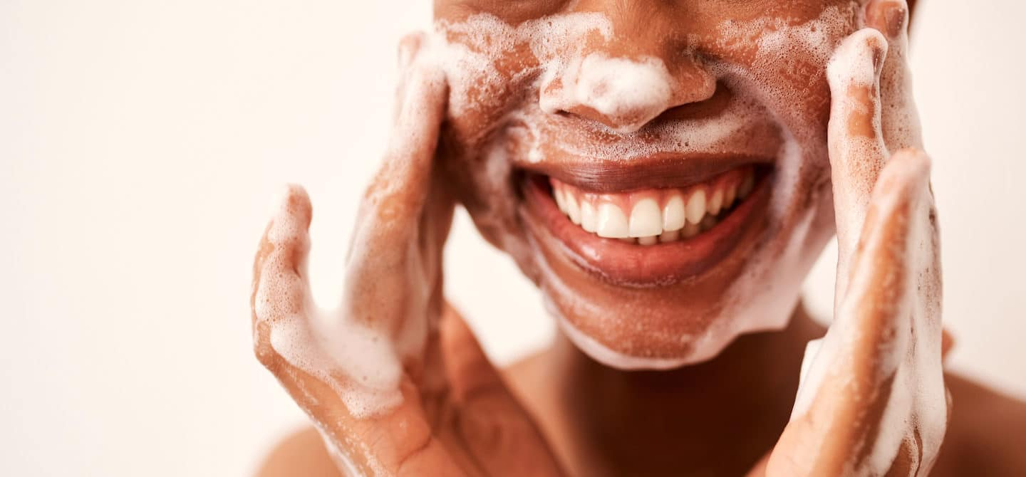 Woman smiling while double cleansing her face