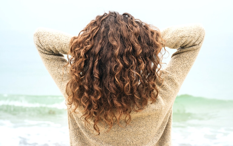 Woman with long curly hair tousling her hair at the beach after eating the best foods for hair growth