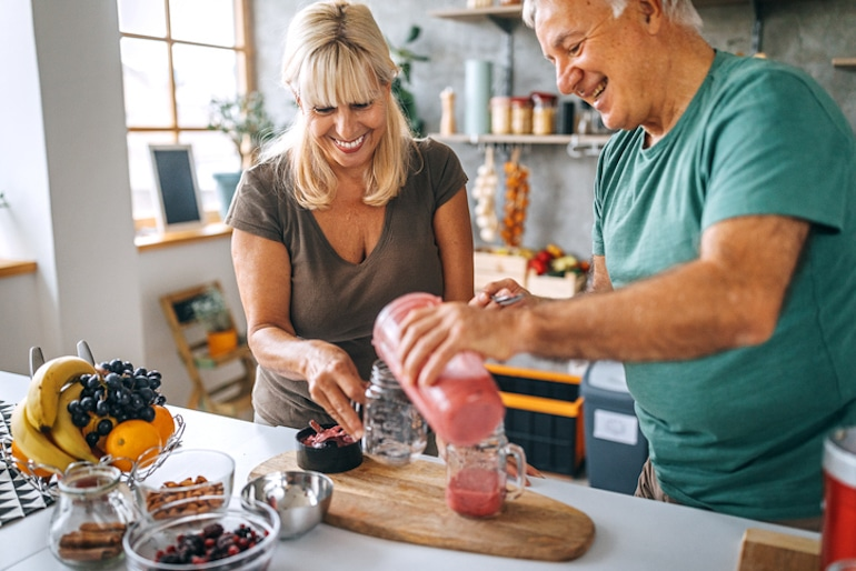 how do nutritional needs change over time? Married couple in their 60s making a vitamin C smoothie to stay healthy with antioxidants and prevent skin aging