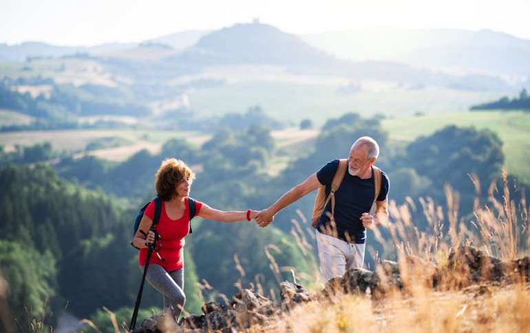 Senior couple holding hands while hiking, which can strengthen relationships and bonding