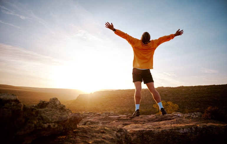 Man celebrating reaching the top of a summit, demonstrating a mental health benefit of hiking