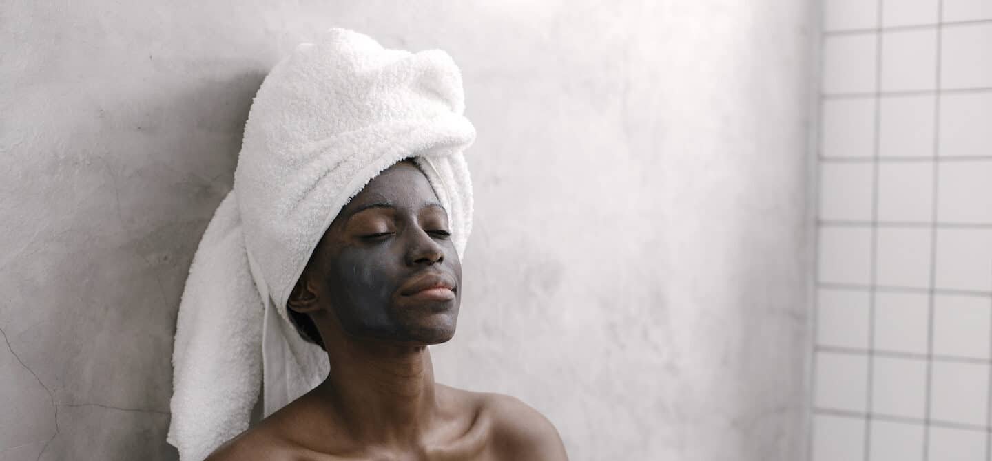 Woman relaxing while benefiting from activated charcoal skincare products