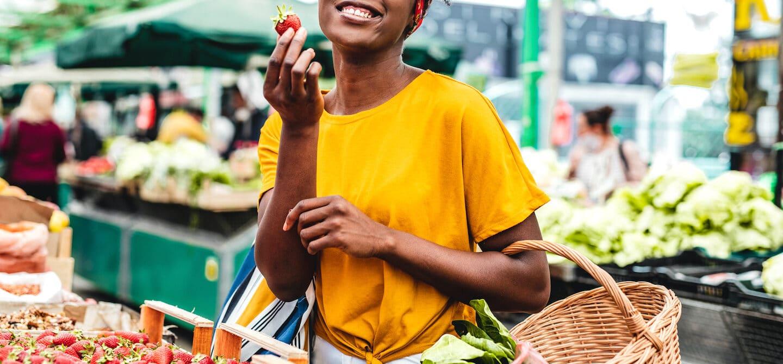 Black woman shopping at farmers market for fresh produce