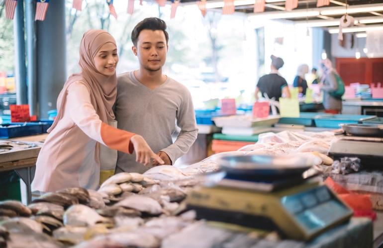 Couple at fishmonger buying fresh fish