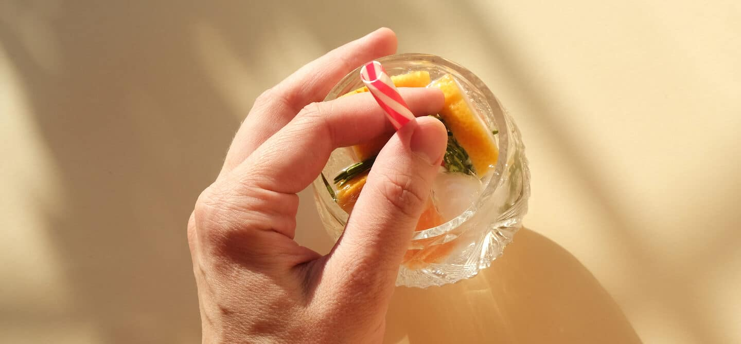 Holding onto straw in seltzer glass with fruits