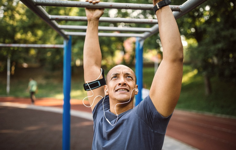 Man exercising in jungle gym after work in the early evening