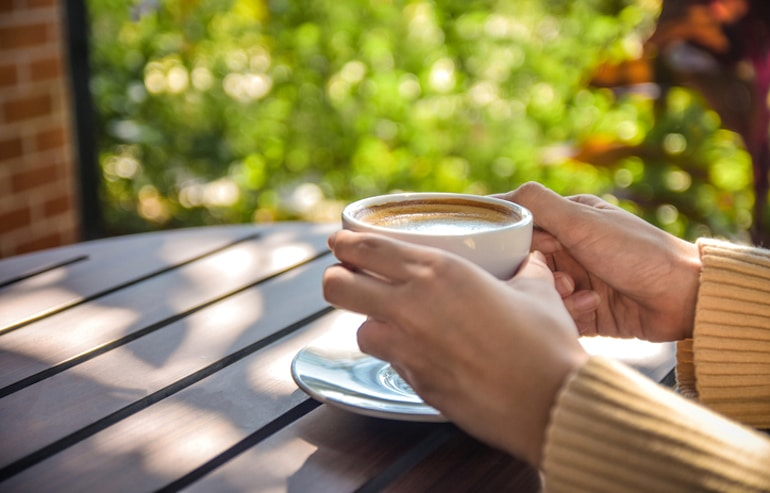 Woman taking her latte outdoors in the morning