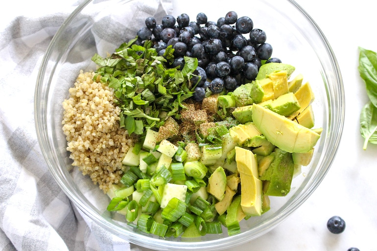 Quinoa, cucumbers, blueberries, avocado, and other veggies in a healthy summer quinoa salad