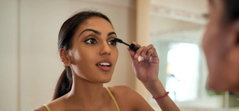 Indian woman applying mascara carefully in the mirror