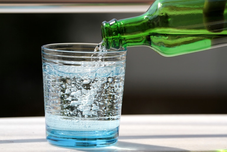 Pouring seltzer into glass