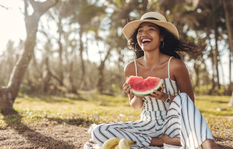 Young woman with hydrated, glowing skin eating watermelon at picnic