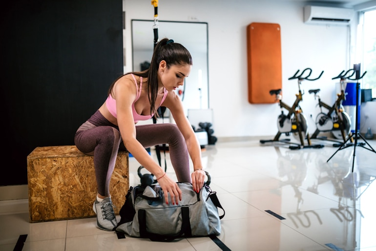 Woman opening her gym bag after working out in the afternoon