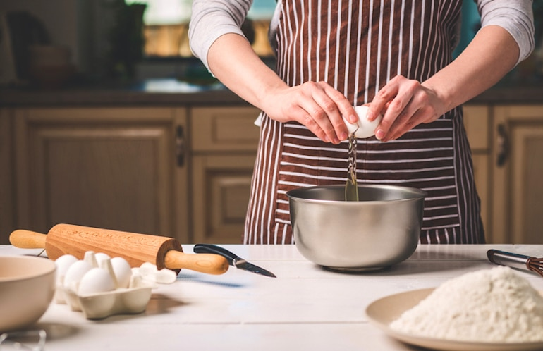Woman breaking white organic eggs into bowl for baking