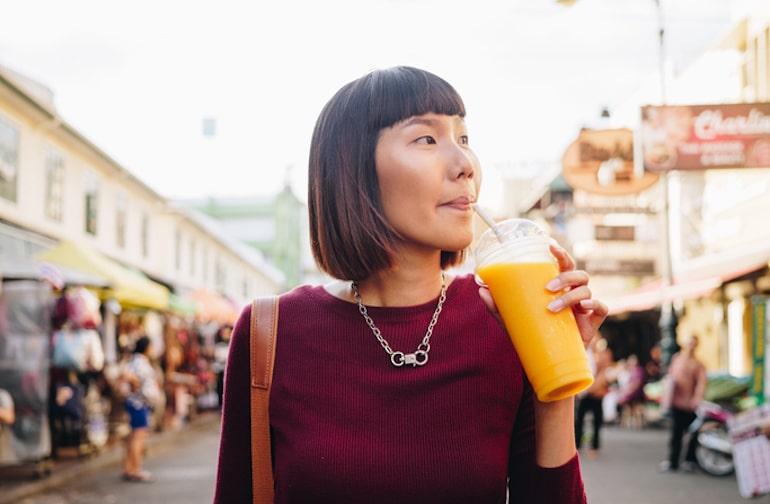 Mujer con piel sana bebiendo jugo de mango en el mercado al aire libre