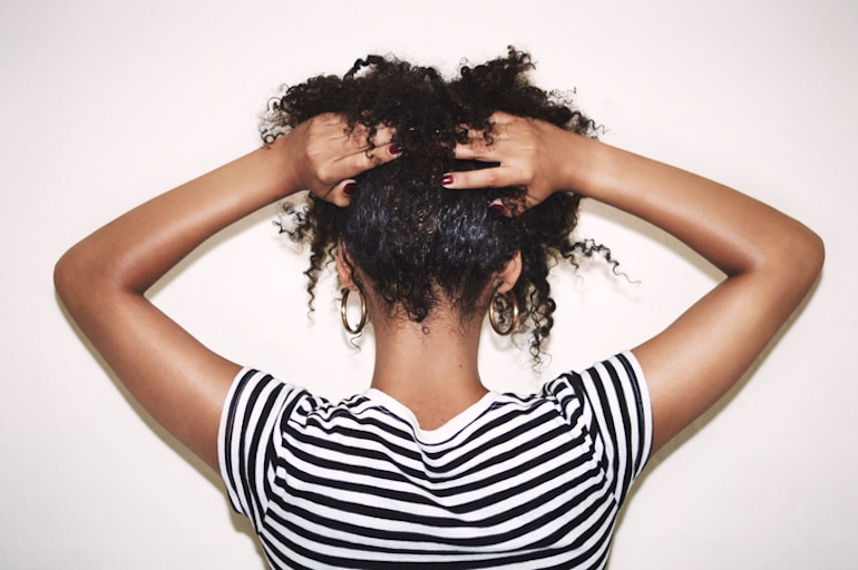 Back of woman's head with her curly hair in hands after taking the best vitamins for hair growth